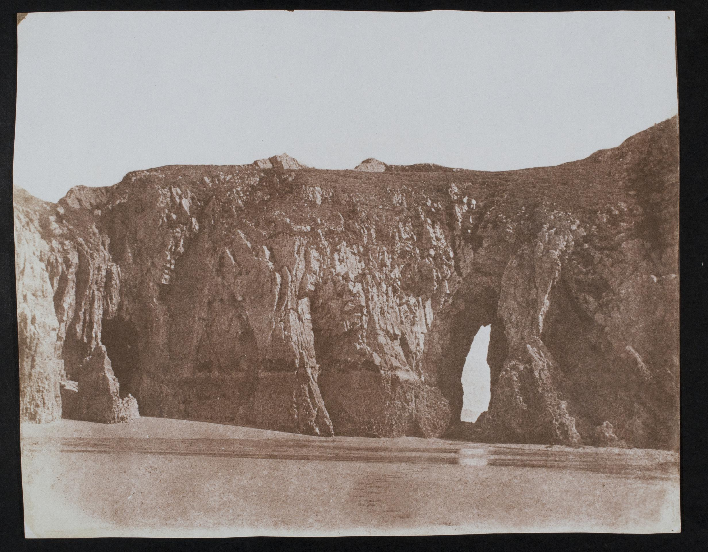 Rock arch in cliff (Three Cliffs Bay?), photograph