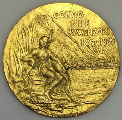 photograph of the reverse of the gold medal showing a female figure in a helmet sat on the bank of a river